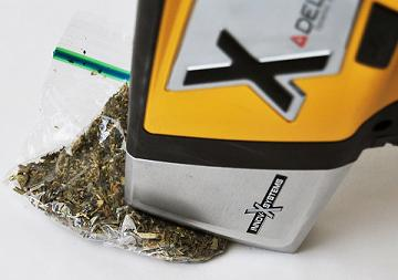 Delta Handheld XRF Analyzer testing a bag of marijuana