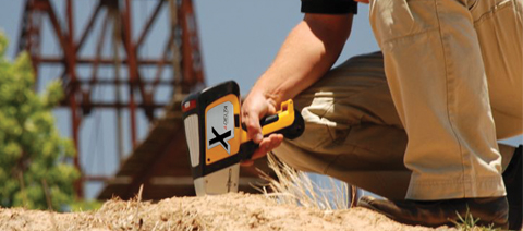 Olympus Innov-X DELTA handheld XRF analyzer analyzing soil in-situ.