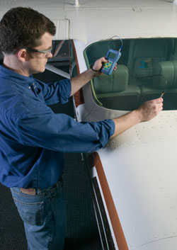 Inspector measure thickness of aircraft windsheild using a 35